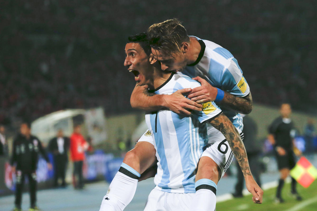 Argentina's Angel Di Maria, left, is embraced by teammate Lucas Biglia after scoring his team's first goal against Chile during a 2018 Russia World Cup qualifying soccer match at the National Stadium in Santiago, Chile, Thursday, March 24, 2016. (AP Photo/ Luis Hidalgo)